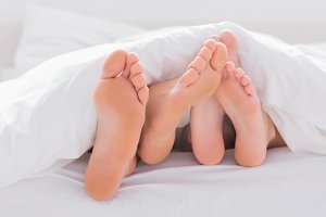 Couple rubbing their feet together under the duvet