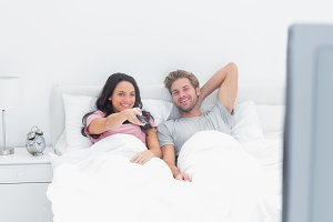 Couple watching tv in their bed