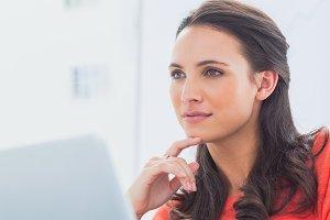 Thoughtful designer sitting behind her desk