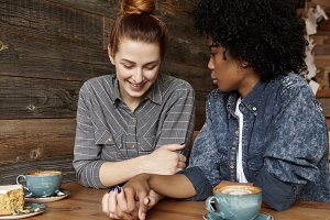Beautiful Caucasian lesbian with hair bun relaxing at coffee shop with her stylish dark-skinned girlfriend in denim shirt. Happy homosexual couple enjoying great time together, holding hands