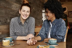 Happy lesbian couple having date at cafe. Cute Caucasian redhead girl holding hands with her dark-skinned female spouse while spending nice time together at restaurant, drinking coffee and eating cake