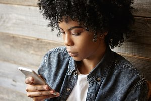Portrait of fashionable young dark-skinned woman with Afro hairstyle having serious look, holding generic smart phone, frowning while reading sms, quarreling with her boyfriend. People and technology