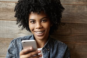Indoor shot of beautiful happy African girl with braces looking and smiling at camera, enjoying free wireless internet connection on her mobile phone, messaging friends online via social networks