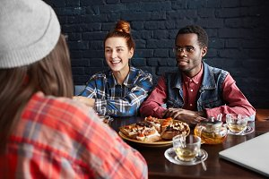 International friendship. Fashionable African male in glasses sitting at cafe table with food next to his cheerful redhead girlfriend, both looking ahead of them and listening to unrecognizable girl