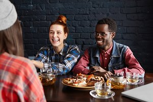 Three students dining at cafe after college. Beautiful girl with ginger hair and stylish African man smiling happily havinglively conversation with their common female friend sitting in foreground