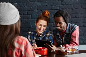 People, leisure, communication and modern technology concept. Happy interracial couple enjoying high-speed connection at restaurant during lunch, browsing internet on digital tablet and laughing