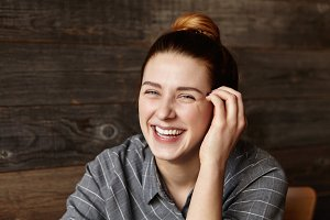 Portrait of happy Caucasian girl with hair bun looking at camera with cheerful smile, holding hand on her face while dining at modern restaurant alone, waiting for her lunch. People and lifestyle