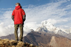 People, mountaineering, hiking and climbing. Rear shot of tourist in red vest standing on edge of cliff, keeping his hands in pockets and admiring picturesque view of snowy peaks in front of him