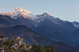Rural life in front of gigantic Himalayas, Nepal. Incredible view of Nepali village with Buddhist flags strung along, spectacular ancient mountains with white craggy peaks standing high in background