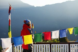 Unrecognizable tourist in red vest standing at white fence of base camp or village, looking at beautiful mountains in front of him, enjoying view during trek in Nepal. Prayer banners in foreground