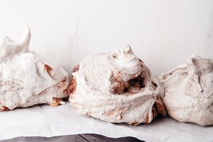 Homemade french meringue on white baking paper with gray towel