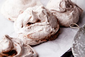 Three homemade french meringues on white baking paper with towel