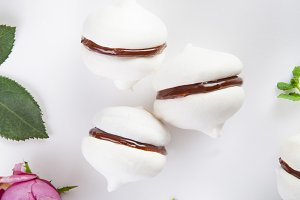 Meringue cookies with chocolate, mint and flowers on white background
