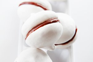 Meringue cookies with chocolate on white background