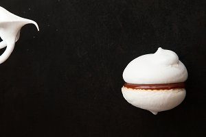 White meringue cookie and mixer whisks on black background