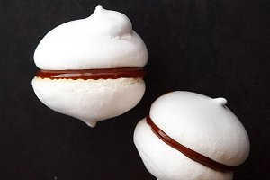 Two white meringue cookies with chocolate on black background