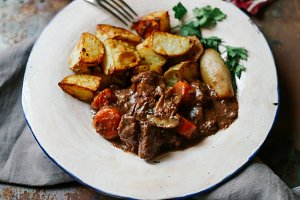 Beef bourguignon in ceramic plate with baked potatoes