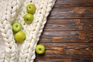 Top view of group of fresh apples with a blanket of thick yarn on brown wooden table texture background from topview