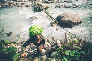 Traveler over river climbing