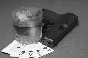 Poker aces, drink and gun