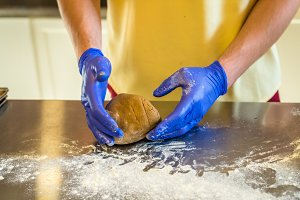 Hands knead dough with gloves