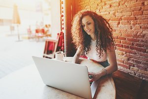 Brunette curly girl with laptop