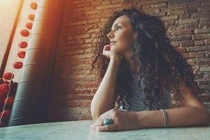 Pensive curly brunette girl in cafe