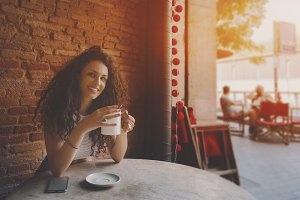 Curly girl in cafe with tea