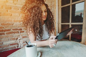 Curly girl in cafe using her gadget