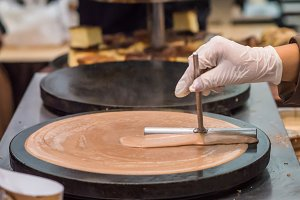 hand prepares chocolate pancake outdoors