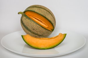 ripe melon with slice on white background
