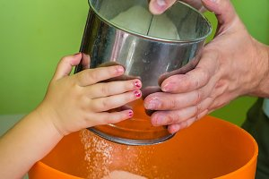 Children and dad hands Sift flour