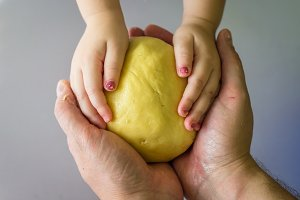 Children and dad hands hold dough