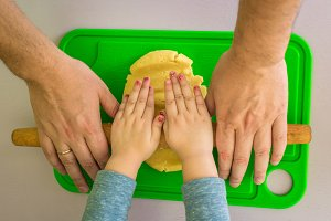 Children and dad hands rolled shortcrust dough