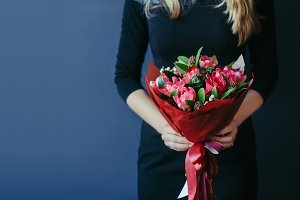 Bouquet of red tulips in girs hands. Unrecognisable.