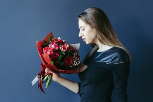 Cute girl with bouquet of red tulips.