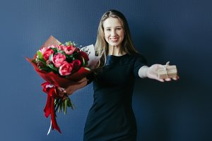 Cute girl with bouquet of red tulips and surprise woodenbox.