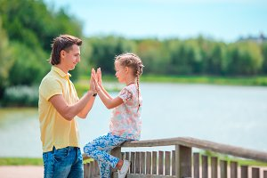 Father and little girl playing outdoors background lake