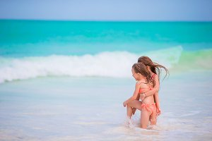 Adorable little girls have fun at waves during summer vacation