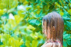 Little happy girl under beach shower on tropical beach