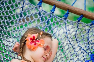 Adorable little girl on summer vacation sleeping in hammock
