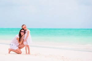 Happy mom and girl on white beach