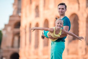 Happy father and little adorable girl in Rome during summer italian vacation background Colosseum