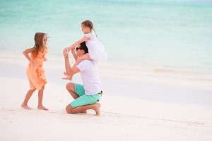Young family enjoying beach summer vacation. Kids and dad having fun together