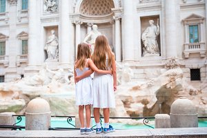 Adorable little girls near the Fountain of Trevi in Rome. Happy kids enjoy their european vacation in Italy