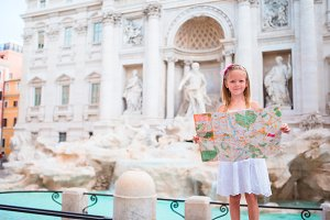 Adorable little girl with touristic map near Trevi Fountain, Rome. Happy kid enjoy italian vacation holiday in Europe.