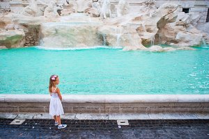 Adorable little girl near the Fountain of Trevi in Rome. Happy kid enjoy their european vacation in Italy