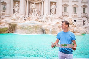Young man with city map iat Trevi Fountain, Rome. Travel tourist guy on holidays in Europe.