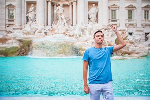 Happy man tourist trowing coins at Trevi Fountain, Rome, Italy for good luck. Caucasian guy making a wish to come back.