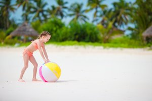 Cute little girl playing with ball on beach, kids summer sport outdoors